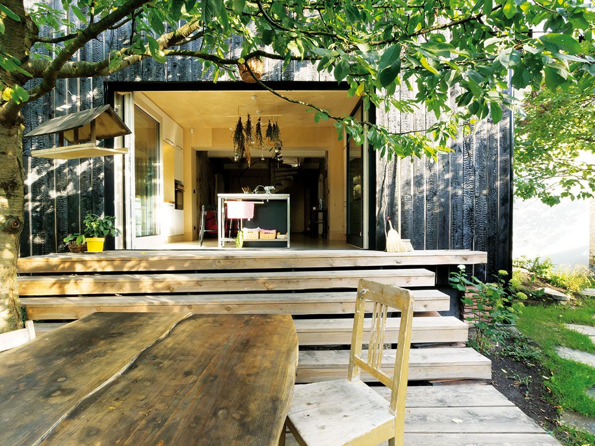 Nový dom siaha od južného okraja pozemku pri lese takmer až ksevernému plotu susedov. Vzadnej časti drevenej dostavby je kuchyňa, ktorá pokračuje ďalej do súkromnej záhrady drevenou terasou.