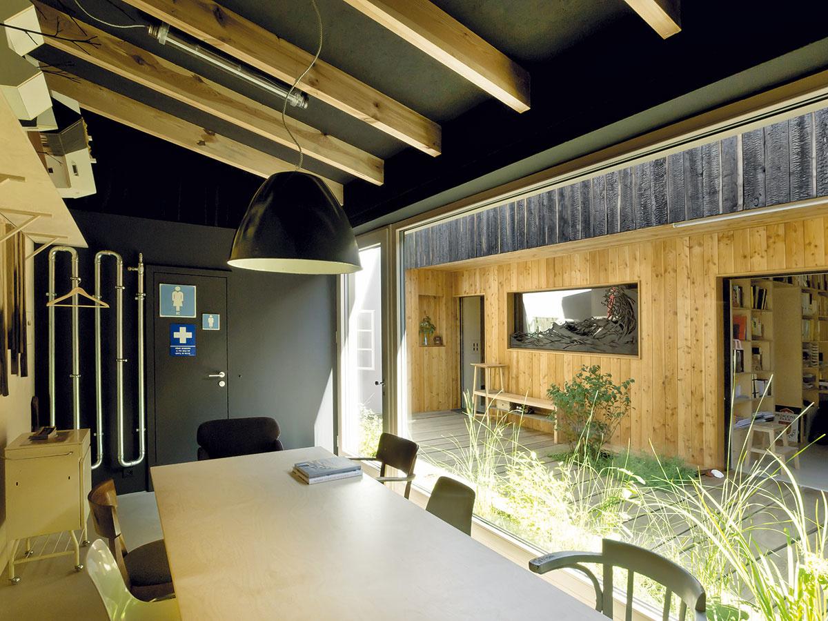 Zasadačka vniekdajšej hospodárskej budove slúži na porady astretnutia sklientmi, oproti, vdrevenej dostavbe, je ateliér architektov čiastočne otvorený až do podkrovia. Veľké zasklené steny vytvorili kontakt medzi oboma pracovnými priestormi.