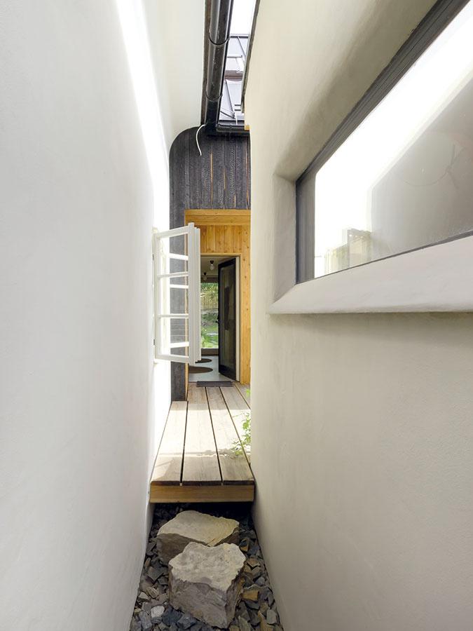 Priehľad medzi starým domom azasadačkou smerom kvstupu do domu, ktorý je jediným spoločným miestnom bývania aateliéru.