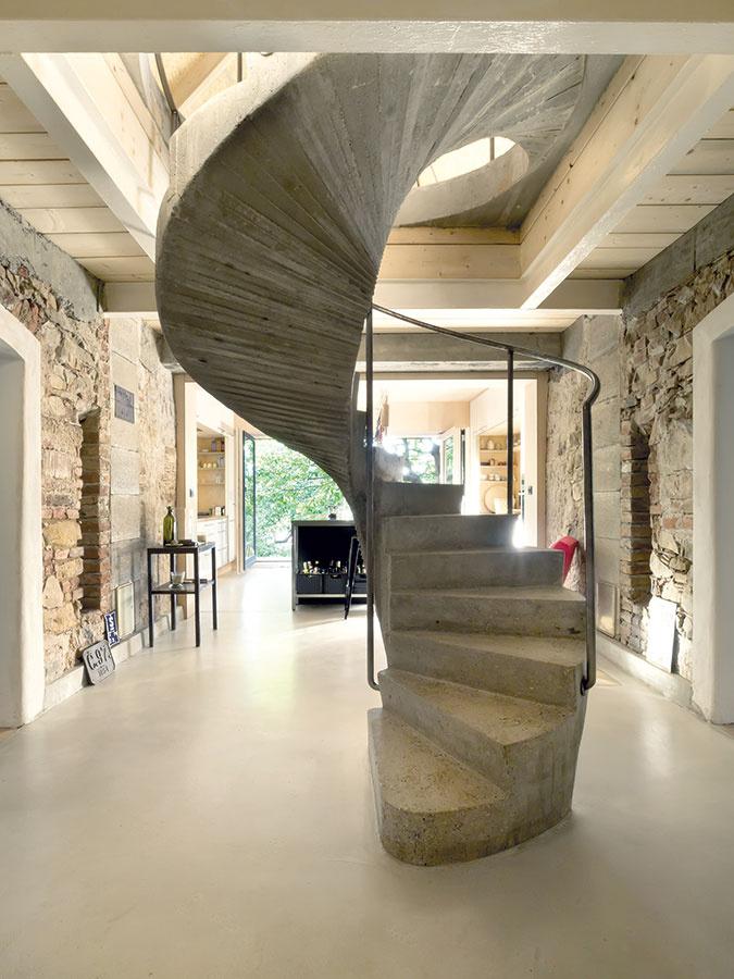 """Vcentre. Byt architektov sa začína halou vmieste kríženia starého anového domu, ktorej dominujú točité schody zmonolitického betónu. Oproti nim, na konci nového domu, je kuchyňa, naľavo od schodiska obývačka, napravo jedáleň. Na poschodí, vpodkroví starého domu, sú dve spálne, kúpeľňa anad kuchyňou miestnosť spríznačným názvom """"lebedín""""."""