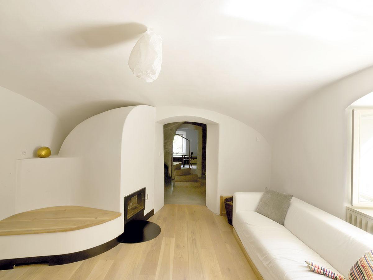 Staromilský minimalizmus. Obývačka skachľovou pecou, knižnicou apohodlnou sedačkou – vďaka jednoduchosti vybavenia vynikol pôvab pôvodných priestorov pod klenutým stropom.