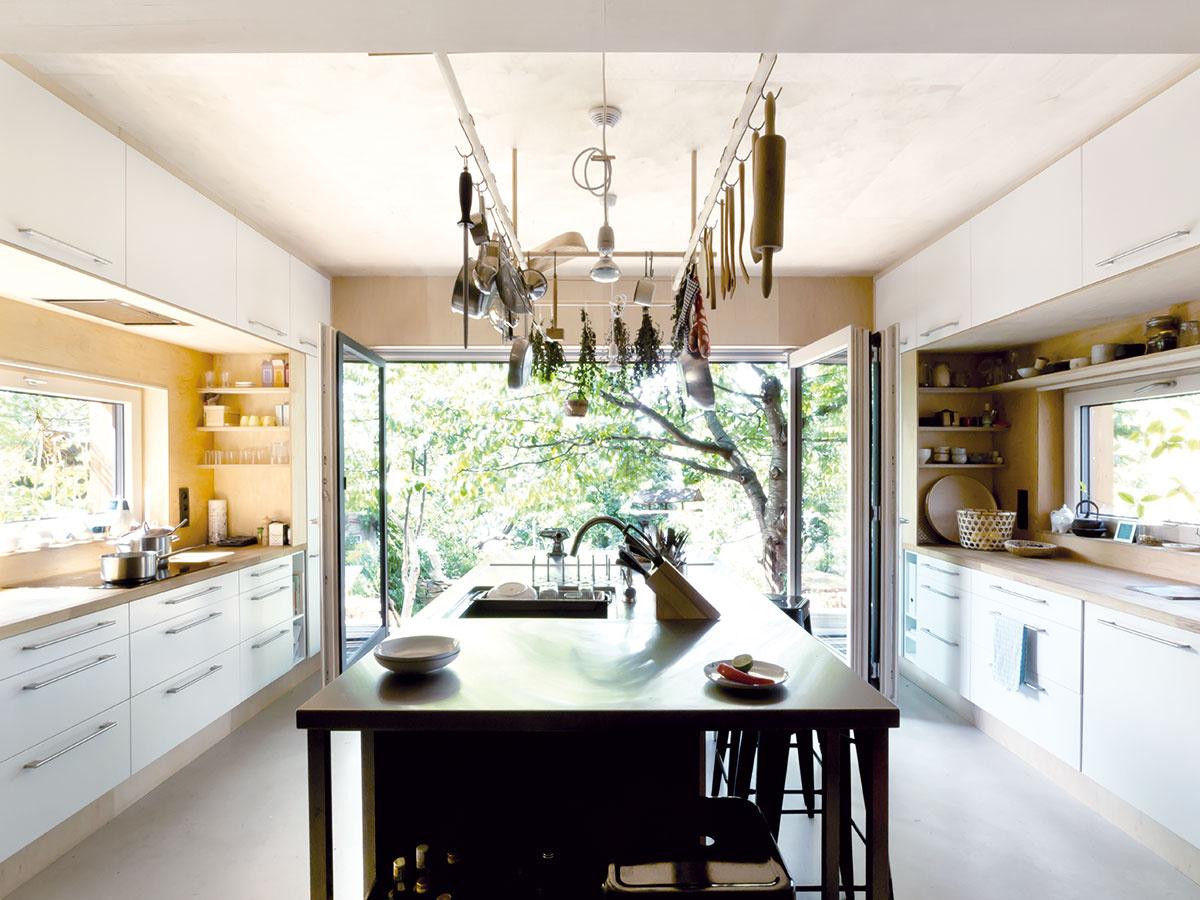 Priestranná kuchyňa sdostatkom pracovných plôch je vtomto dome stredobodom diania. Vďaka jej umiestneniu na konci nového domu aspojeniu so záhradou sa môže drevená terasa, ktorá na ňu nadväzuje, zmeniť na vzdušnú letnú jedáleň.