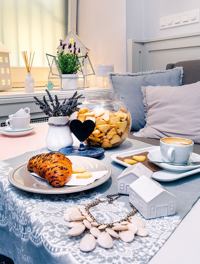Tlmená farebnosť bielej a odtieňov sivej doplnená jemnými pastelkami je jedným z poznávacích znamení kaviarne. Podobné farby môžu naplniť pokojom a harmóniou aj vašu domácnosť.