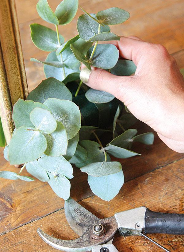 Rastliny skráťte záhradníckymi kliešťami na potrebnú dĺžku apostupne ich pozapichujte do aranžérskej hmoty. Začnite eukalyptom, pomocou ktorého vytvoríte základný tvar aranžmánu asúčasne prekryjete aranžérsku hmotu.