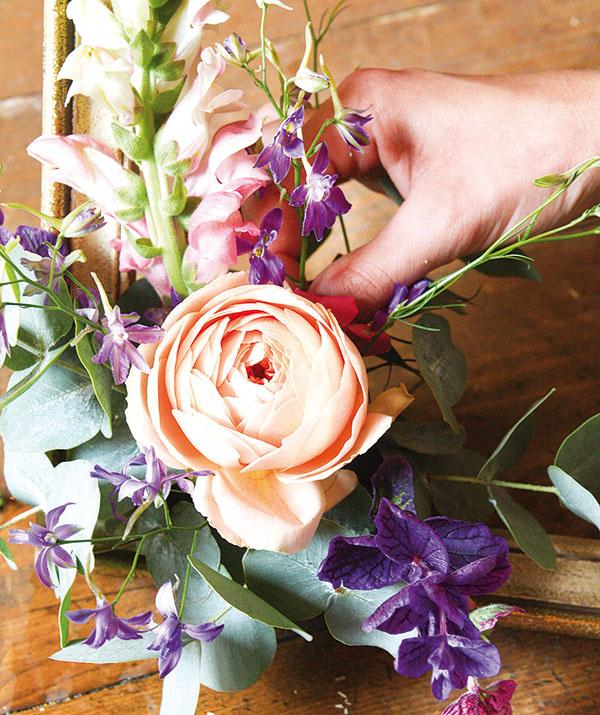 Pokračujte ružou, nad ňu umiestnite papuľku ado priestoru pod ňou zase hluchavku. Takto postupne získate želaný tvar aranžmánu vtvare písmenaL. Postupne do medzier povpichujte zvyšné rastliny, kým aranžérsku hmotu úplne nezaplníte.