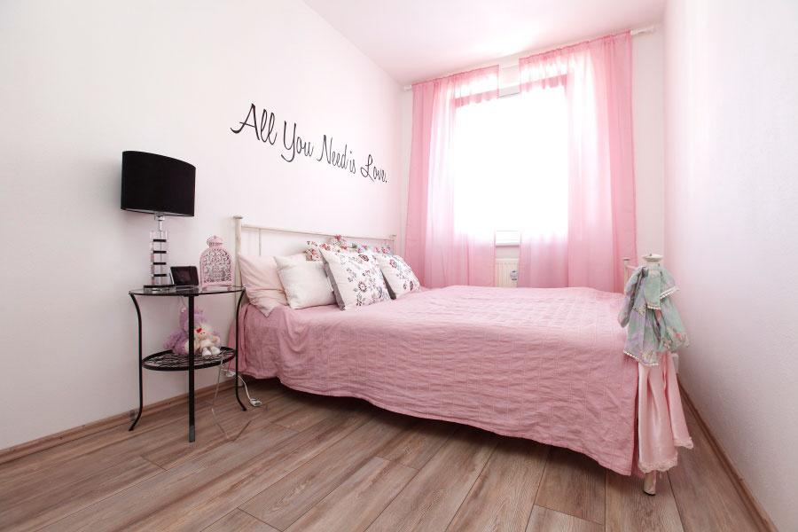 Ružová sa stala síce dominantou, ale vspálni jej dodáva dramatickosť čierny nápis na stene ačierna farba na stolovej lampe.