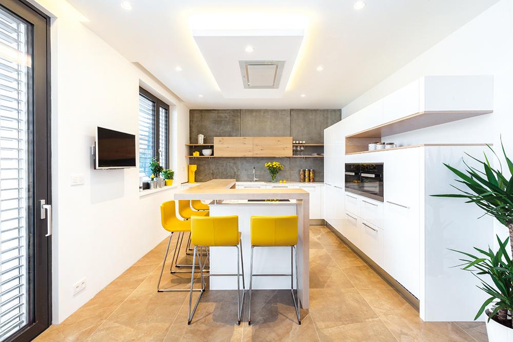 Kombinácia lesklého bieleho laku, matnej drevenej dyhy a betónovej zásteny má správnu mieru, je decentná, elegantná aj nápaditá, navyše sa dá tento základ skombinovať s rôznymi doplnkami. Má teda všetky predpoklady stať sa nadčasovým riešením