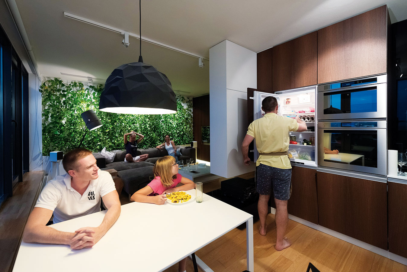 """Na rozhraní kuchyne aobývačky umiestnili architekti atypický kus nábytku – zjednej strany je """"podložkou"""" pod televízor areceiver, zdruhej bielou kuchynskou skrinkou."""