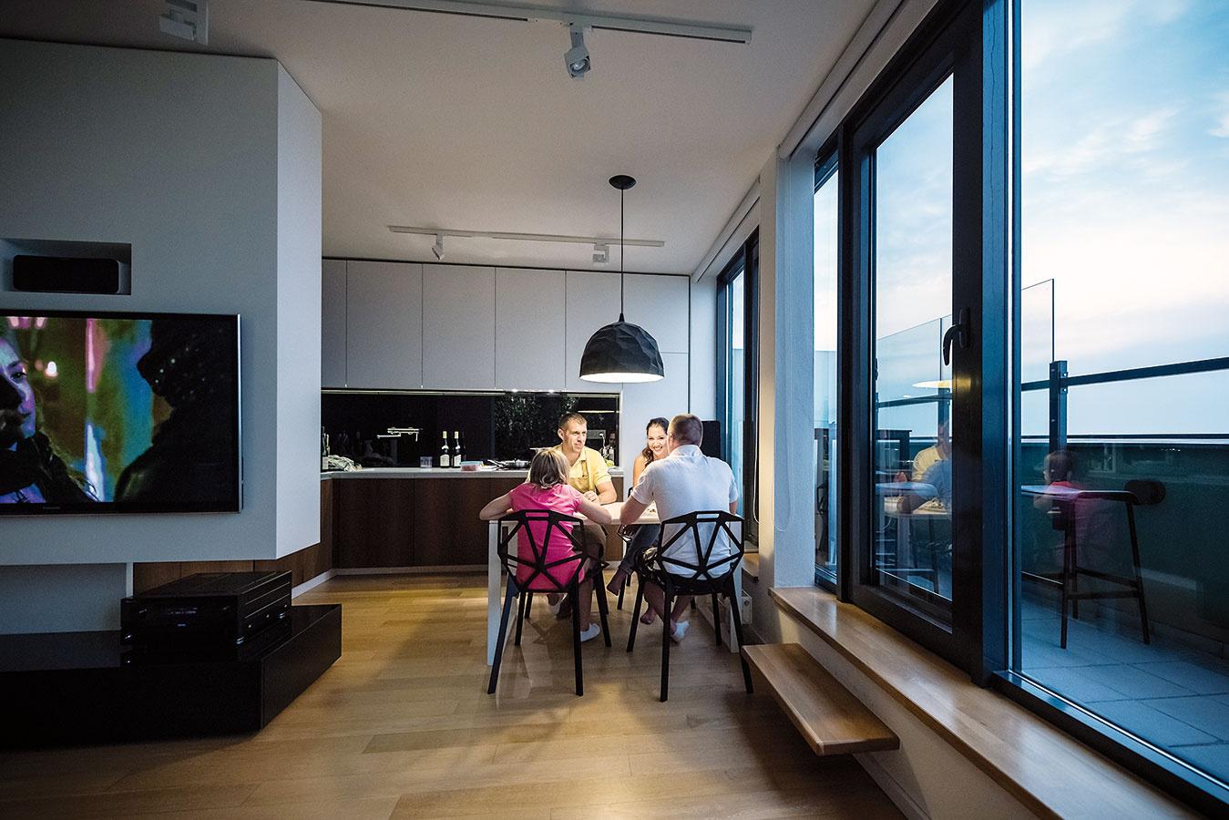 Jedálenský stôl medzi kuchyňou aobývačkou sa spolu stelevíznou skrinkou podieľa na vytvorení hranice medzi dvoma zónami denného priestoru. Biely stôl dopĺňa čierna lampa ačierne stoličky, ktoré možno využiť aj vexteriéri.