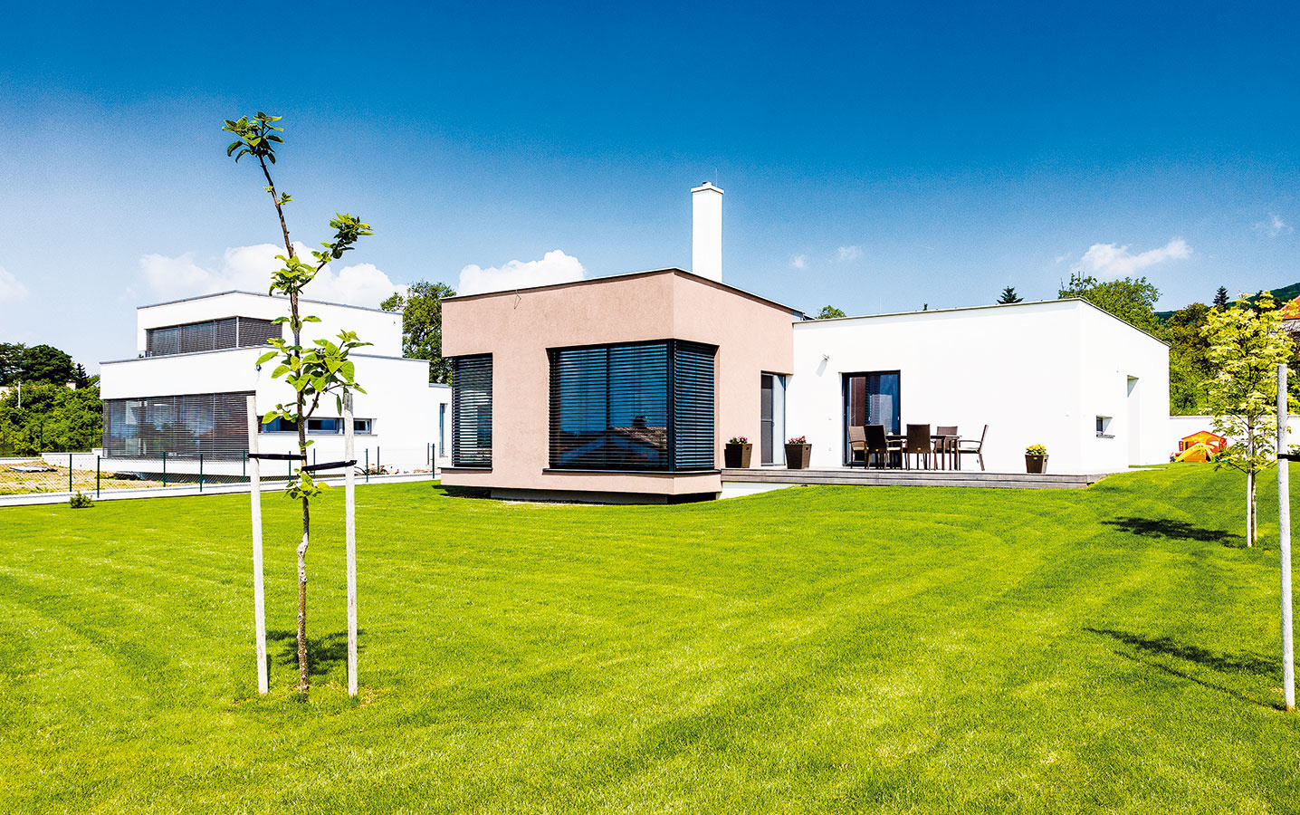 Veľké zasklené plochy prinášajú do interiéru nielen denné svetlo, ale aj solárne zisky. Aby sa v lete interiér neprehrieval, nechýba vonkajšie tienenie.