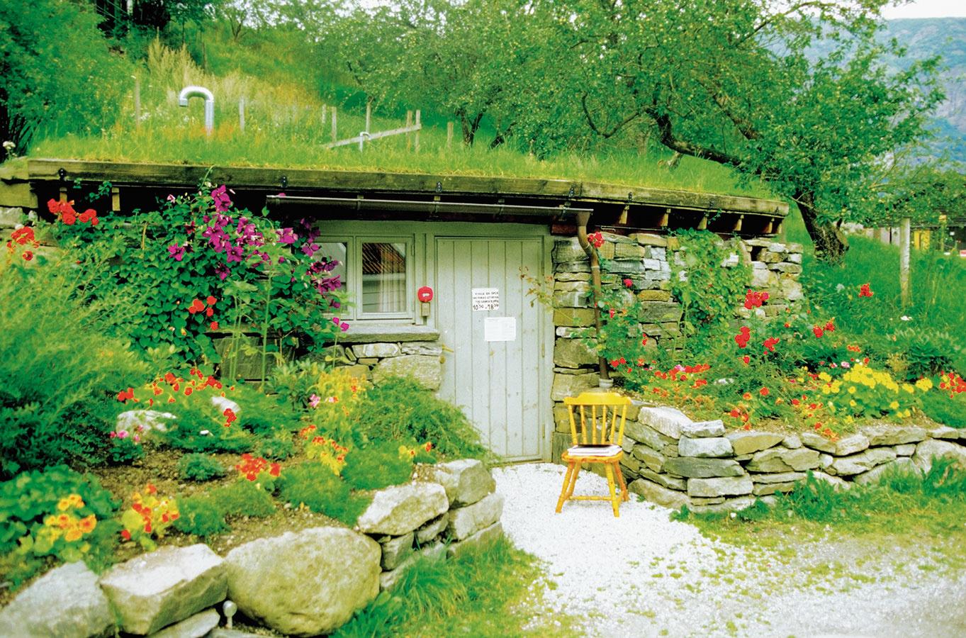 Záhradný domček môže byť vytvorený aj vo svahovitej záhrade. Namiesto strechy rastie tráva avstupné časti spríjemňujú rastliny. Slnečné miesta sú vhodné na pestovanie letničiek, ktoré kvitnú do neskorej jesene. Každoročne si tento priestor možno vysadiť inak.
