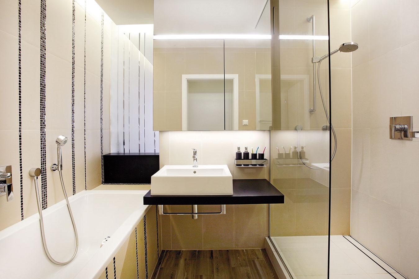 Vkúpeľni bol použitý dekor pásikov, ktorý sa objavuje aj na zrkadlách. Vďaka kombinácii sbéžovou ačiernou farbou obkladov amozaík tak opäť nadväzuje na zvyšok bytu. Denné svetlo prúdi do kúpeľne cez plochu zpieskovaného skla, ktorá ju zároveň oddeľuje od kuchyne.