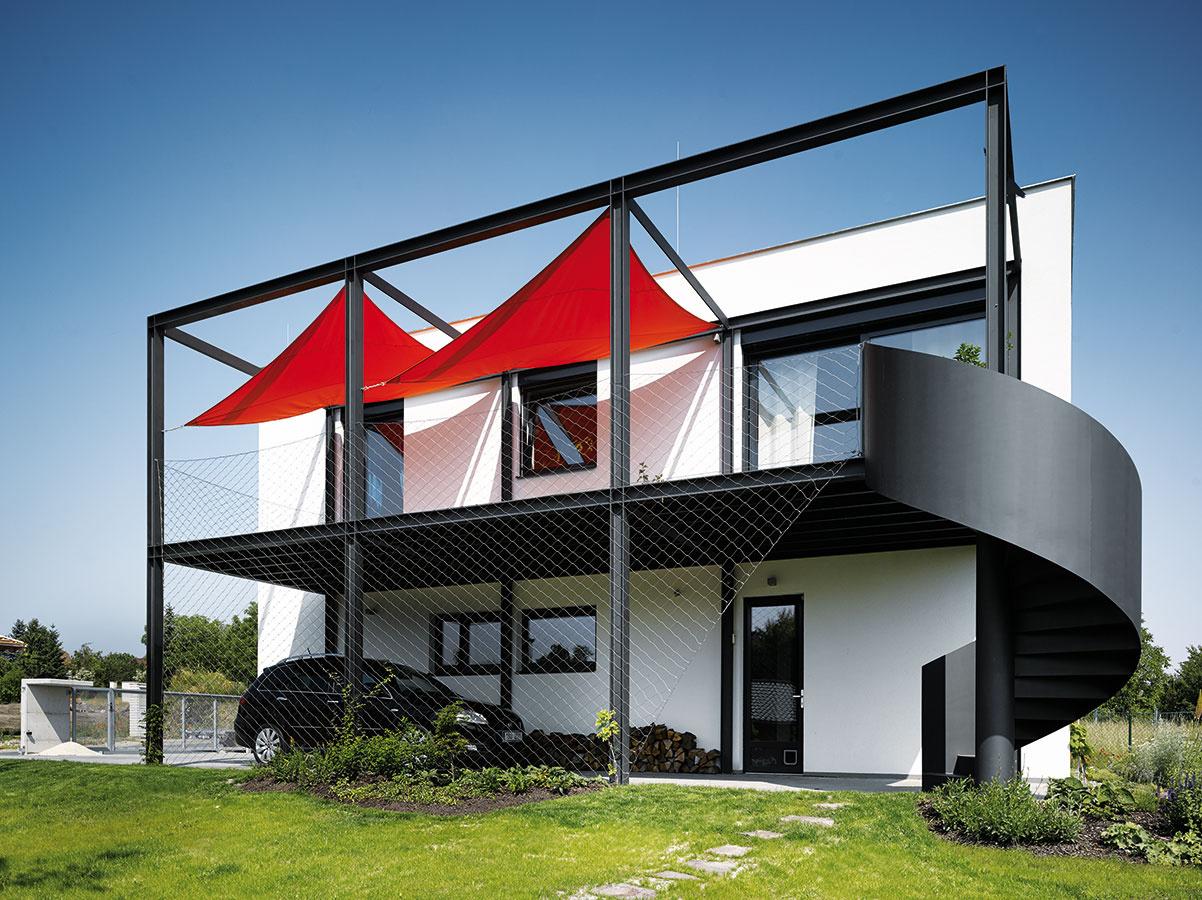 Nápad scharakterom. Oceľovou konštrukciou, ktorá lemuje južnú fasádu, dodali architekti Stempel aTesař jednoduchému domu originalitu azároveň splnili viaceré praktické požiadavky – vspodnej časti funguje ako prístrešok na autá, vhornej sa využíva ako terasa.