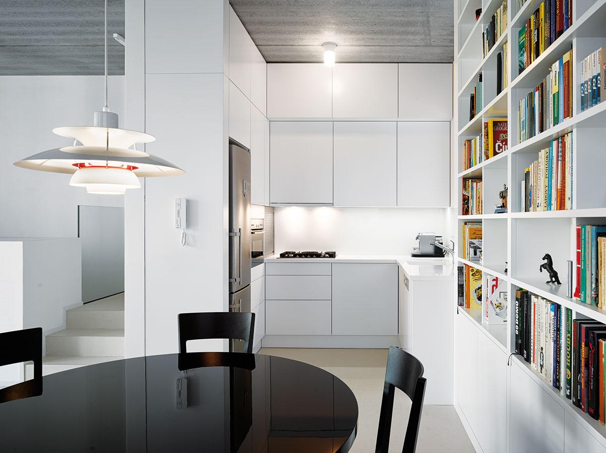 Do výšky. Kuchyňa zaberá pomerne malú plochu, jej priestorovú úspornosť však kompenzujú skrinky vystavané až po zvýšený strop.