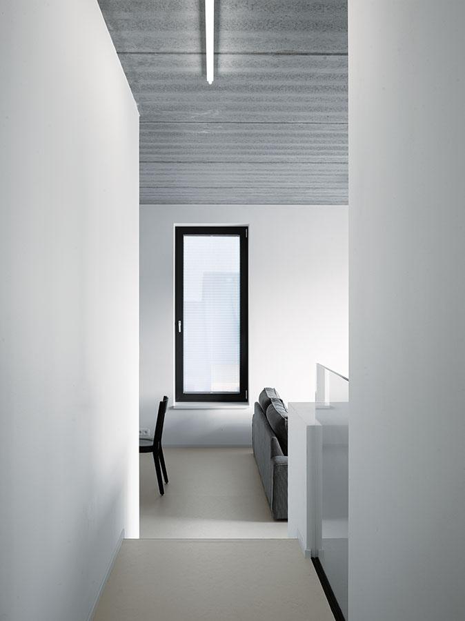Proporcie apriehľady boli vinteriéri dostatočne zaujímavé na to, aby ho architekti ponechali farebne striedmy –lesklá liata podlaha ahladké biele steny príjemne kontrastujú sdrsným sivým povrchom stropu zpohľadového betónu, akcentmi sú čierne okenné rámy. (Pohľad znočnej zóny do dennej)