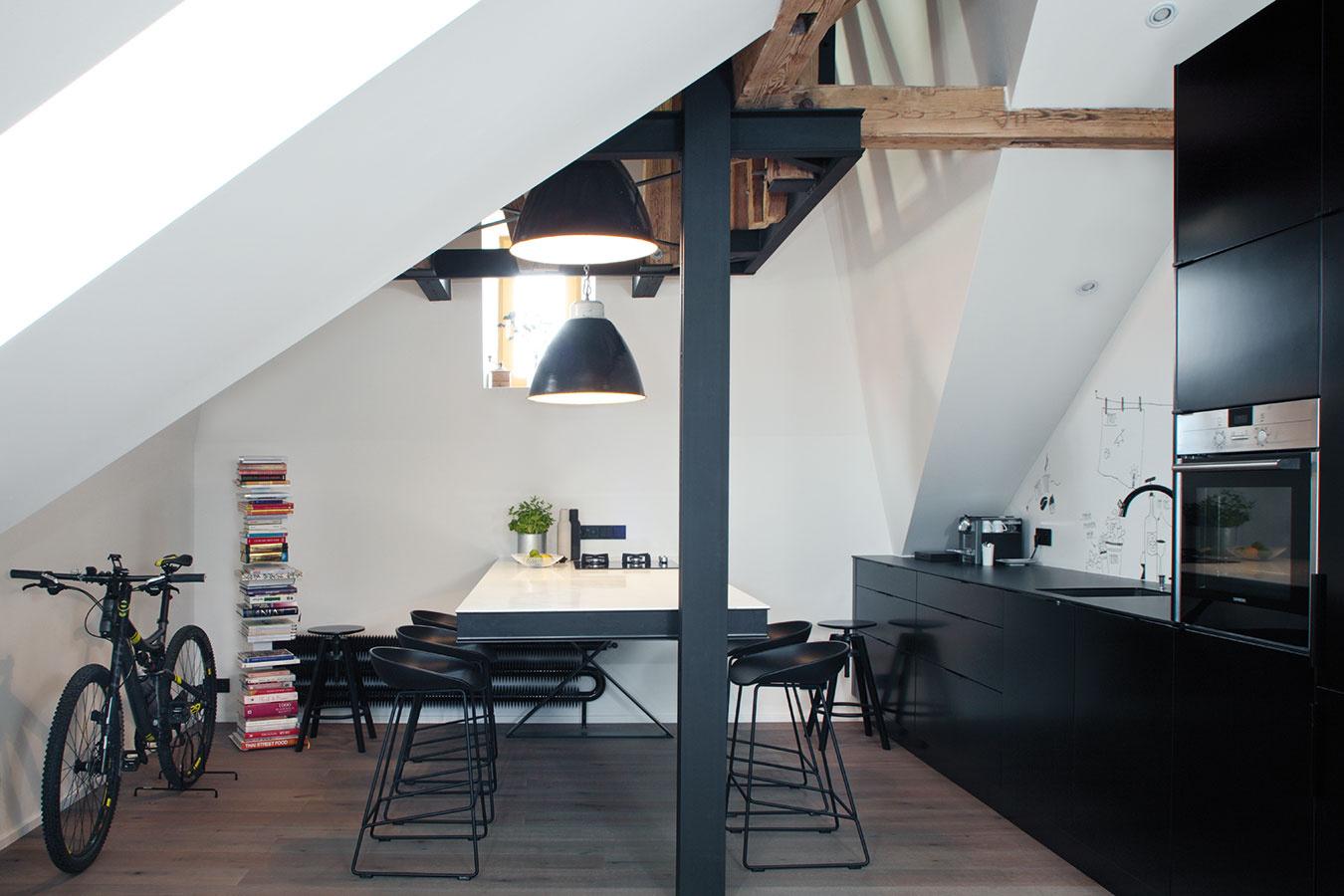 Stolovanie pod vežou. Podkrovie si majitelia vybrali pre jeho atypické proporcie, šikminy avysoké stropy, ale najmä pre vežu, ktorá zasahuje do bytu. Husté trámy jej konštrukcie boli nahradené niekoľkými oceľovými väzníkmi astĺpom, vďaka čomu vzniklo priamo pod vežou ideálne miesto na jedálenský stôl.