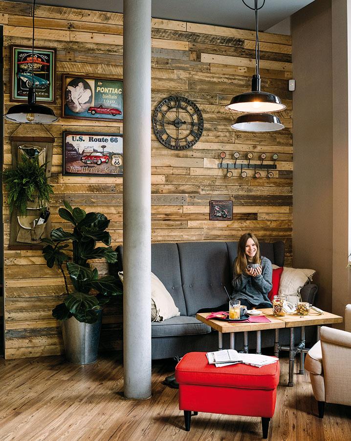 Stena obložená drevom vkombinácii spodlahou sdreveným dekorom, elegantne pôsobiace kreslá, industriálne stolíky aAmerikou inšpirované doplnky vytvárajú pestrú kompozíciu, ktorá nenudí azároveň pôsobí veľmi vkusne.