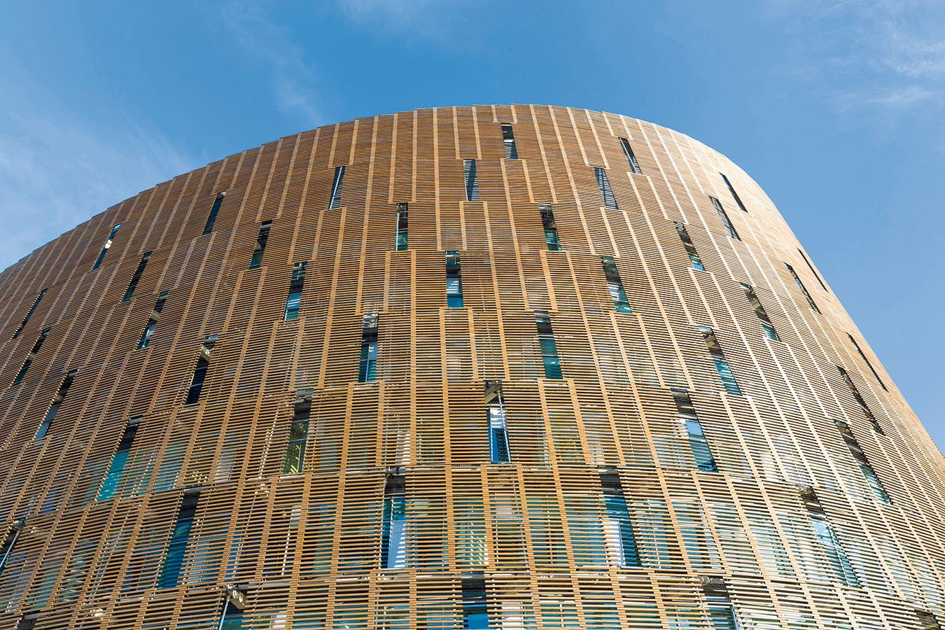 Drevený obklad vo funkcii tienenia fasády pred nadmerným slnečným žiarením zároveň architektonicky dotvára budovu