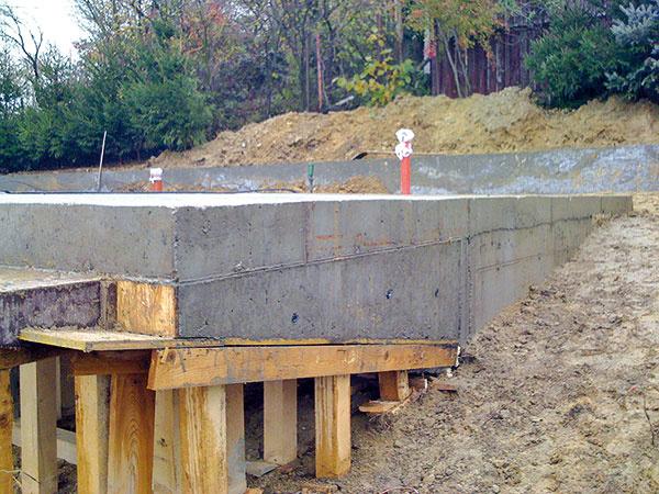 Dom je založený na základových pásoch zprostého betónu so základovou škárou siahajúcou do nezamŕzajúcej hĺbky. Základy sú zbetónu B 20, aj podkladový betón má rovnakú triedu. Pod základovými konštrukciami aj podlahovými vrstvami sa nachádza zhutnené podkladové štrkopieskové lôžko shrúbkou 150mm.