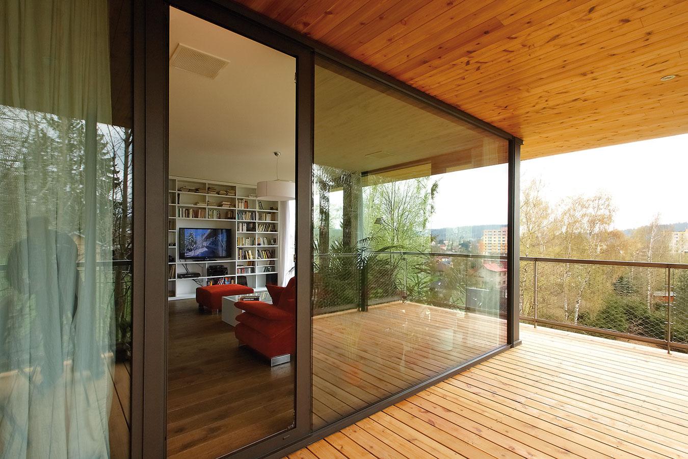 Obývacia izba plynule prechádza do terasy. Veľké sklené dvere, ktoré sa tiahnu až po strop, dodávajú priestoru vzdušnosť ainteriér domu krásne presvetlia. Výhľad zokna neraz zaujme majiteľov domu viac ako práve vysielaný televízny program.