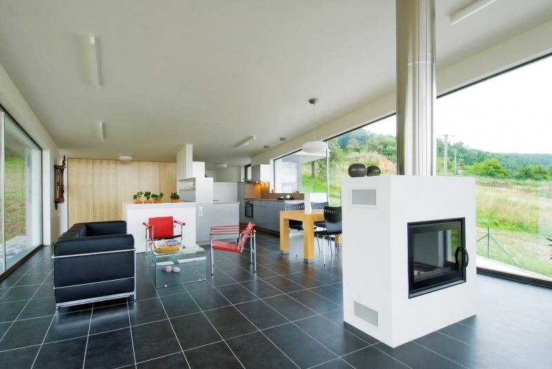 Spoločný obývací priestor je rozdelený na vstupnú halu, kuchynskú časť a na relaxačnú zónu s obojstranným kozubom. Na antracitovej keramickej dlažbe, ktorá korešponduje s terasou z bridlice vynikne nábytok podľa návrhu Le Corbusiera.