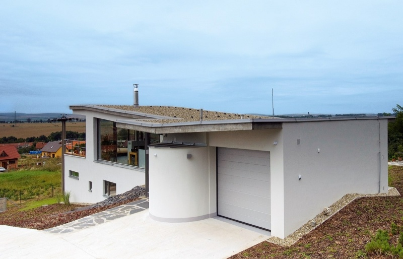 Dom má zelenú strechu, ktorá sa zvažuje do stredu stavby, kde je umiestnené odvodnenie.