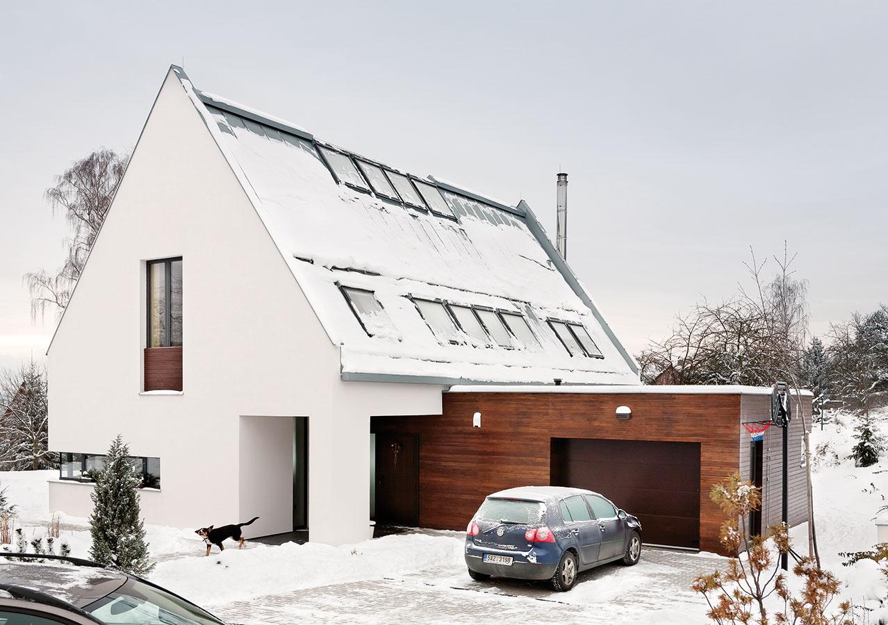 Hlavnú hmotu domu stradične tvarovanou strmou sedlovou strechou dopĺňa kváder garáže, ktorú okrem tvaru odlišuje aj poňatie fasády – tmavý drevený obklad spriznanými škárami pôsobivo kontrastuje sbielou omi etkou.