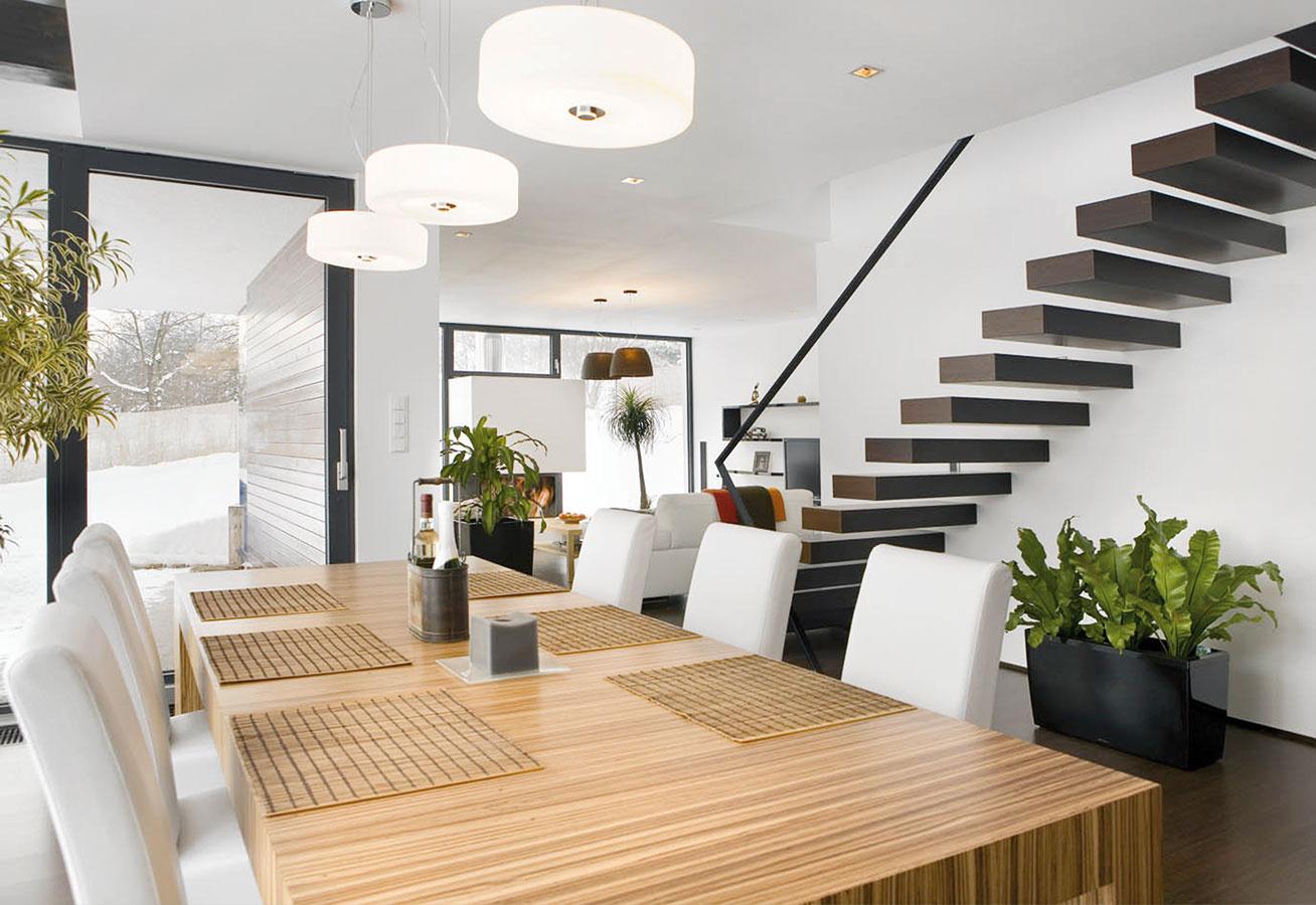 Dve minimalistické schodiská pretínajú vnútorný priestor domu. Zprízemia do podkrovia vedú jednoduché drevené stupne votknuté do steny – rovnaký dekor (wenge) majú aj všetky drevené podlahy vdome. Vpodkroví ich vystriedajú strmé kovové schody.