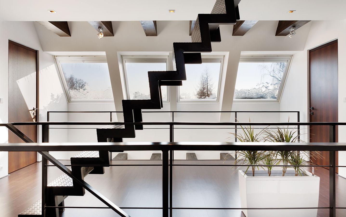 Zgalérie vprvej úrovni podkrovia sa vstupuje do spální ahlavnej kúpeľne. Všetky tri úrovne interiéru prepája pôsobivý priestor, čiastočne otvorený vcelej výške domu abohato osvetlený strešnými oknami VELUX.