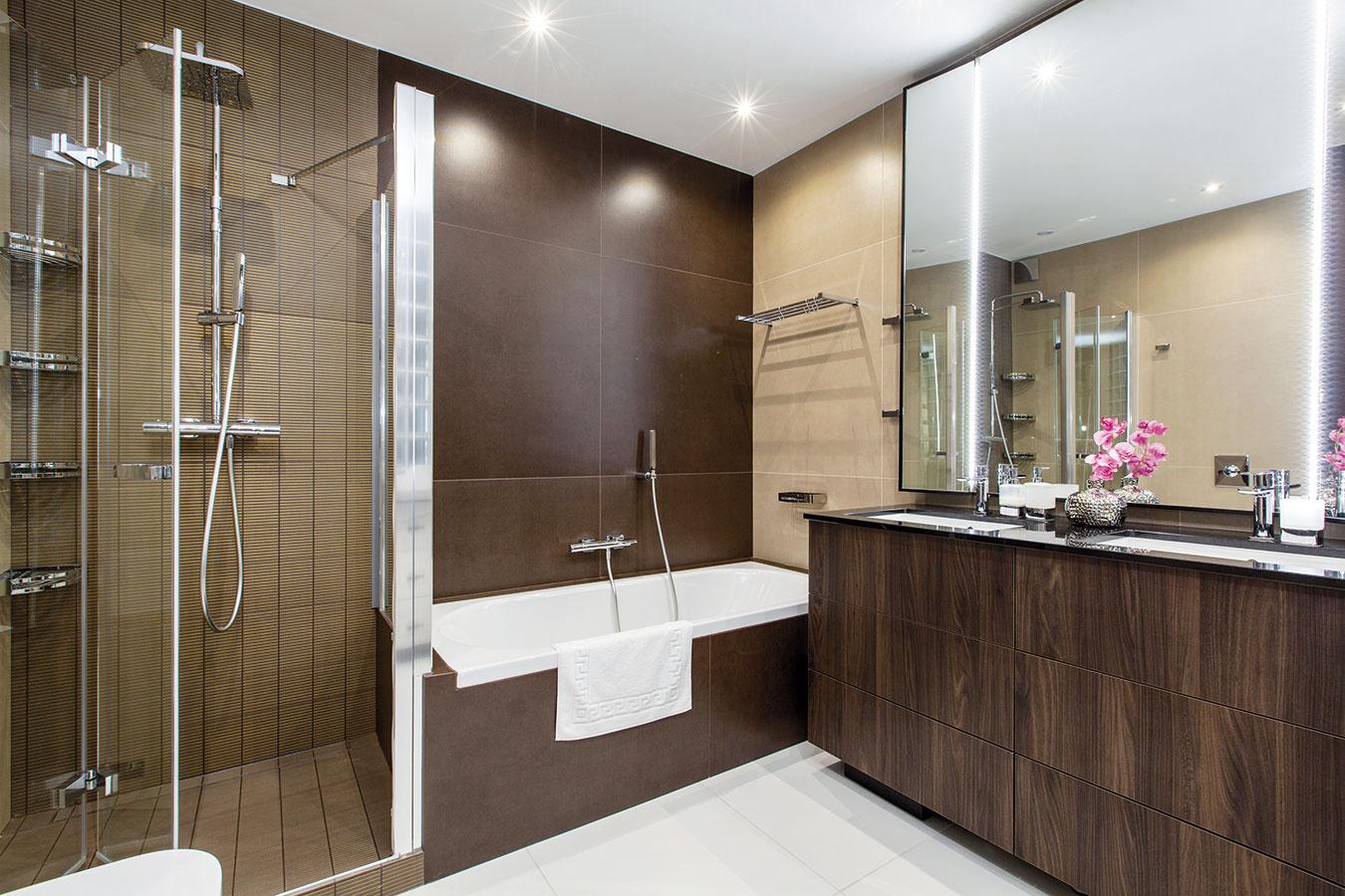 Elegantná farebnosť charakterizuje aj kúpeľňu. Tmavé veľkoplošné obklady vytvárajú pocit elegancie aluxusu, ich tmavosť zmierňuje biela podlaha. Decentnou čerešničkou na torte je zopár zlatých detailov vsprchovacom kúte aelegantný nábytok vyrobený na mieru.