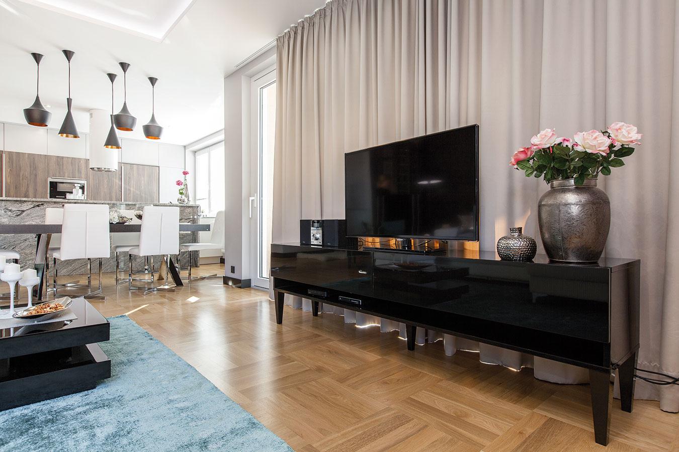Dizajn na mieru. Stolík pod televízor vyrobil podľa Kamilinho návrhu stolár. Hodvábny koberec, príjemný na dotyk, oživuje obývačku farbou aj štruktúrou. Ladia sním aj dvojvrstvové závesy, ktoré sú zjednej strany béžové azdruhej jemne tyrkysové.