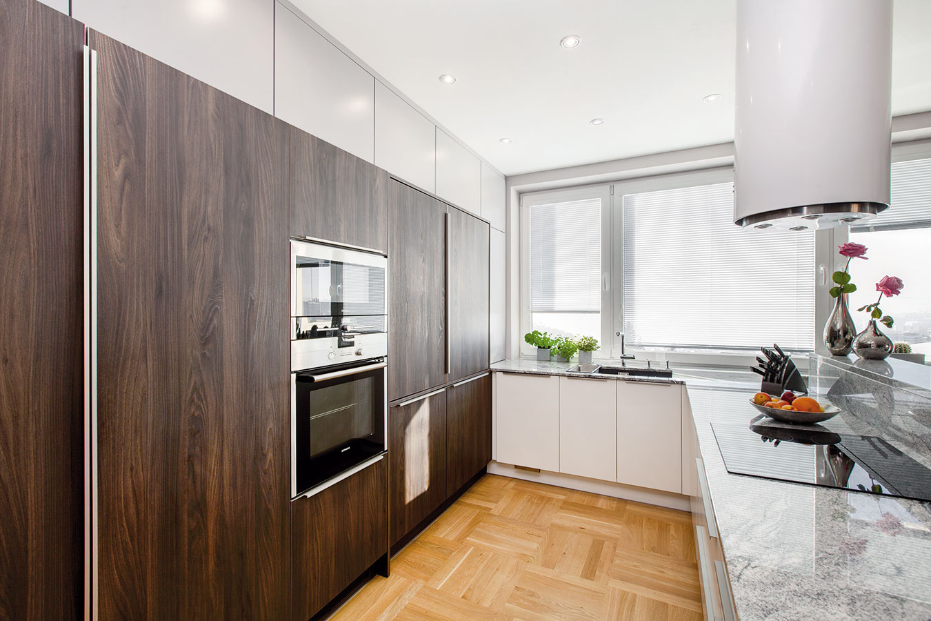 V zadnej časti kuchyne, ktorá je vduchu dnešných trendov zložená zo samých vysokých skríň, sú zabudované spotrebiče. Keďže úložných priestorov nie je vkuchyni nikdy dosť, sivá plocha okolo je vyskladaná zo skriniek – vďaka dvierkam sotváraním push-to-open však pôsobia ako stena.