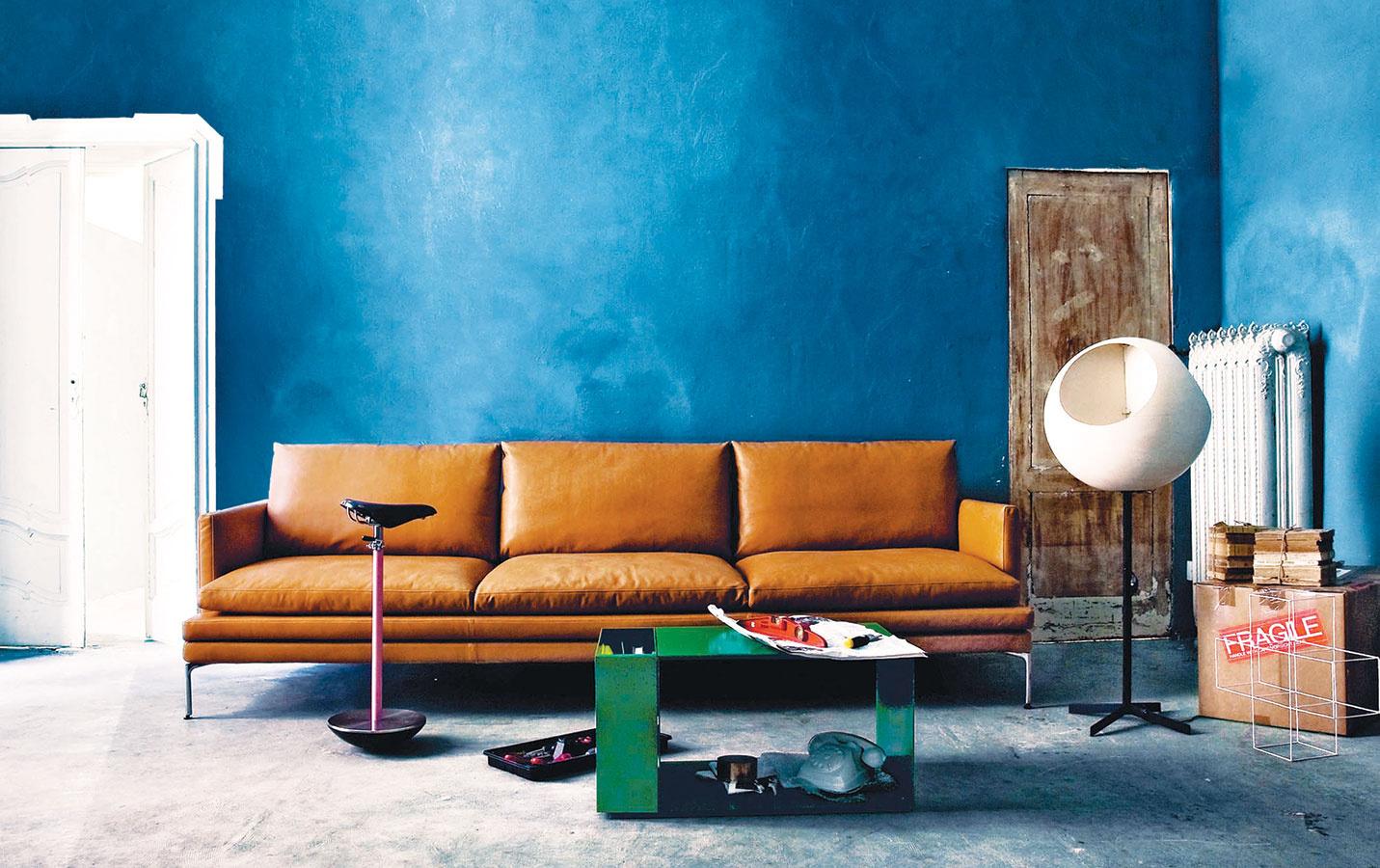 Pred výraznou modrou stenou pekne vynikne sedačka zaodetá v hnedej koži, akou je napríklad modulárna sedacia súprava William od značky Zanotta. Ak vám nevyhovuje kožená úprava, v ponuke nájdete aj rôzne látky. (Predáva DESIGNPROPAGANDA.)