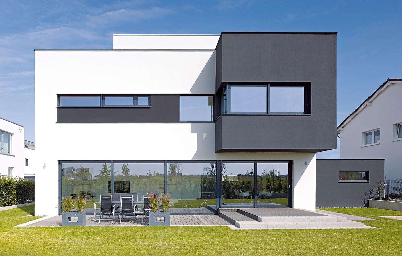 Prelínanie. Okenné pásy, posuvné dvere na terasu apevné zasklenia vytvárajú horizontálne zárezy do čiernych abielych blokov fasády. Všetky transparentné prvky zjednocujú štíhle línie hliníkových okenných profilov velegantnom sivom odtieni. (Pohľad zo záhrady)