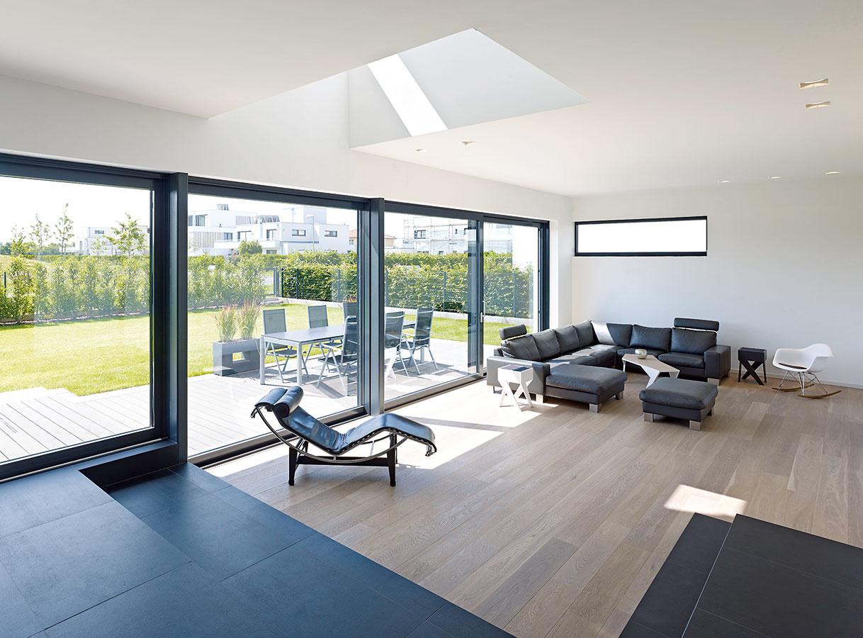 Hra spriestorom apriehľadmi. Obývačka je vďaka niekoľkým schodíkom oniečo vyššia než susedná jedáleň azároveň je vysokým priehľadom spojená sposchodím. Príjemný plynulý priechod do záhrady sprostredkúva veľkorysé zasklenie avonkajšia terasa.