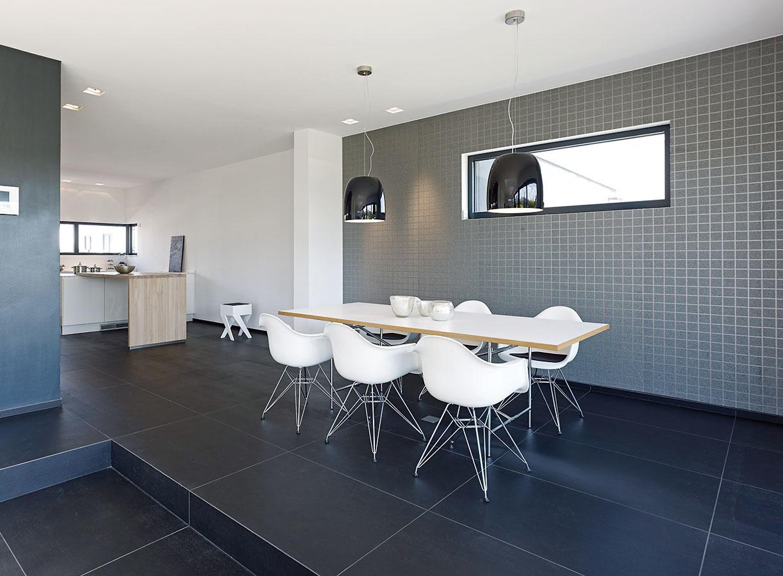 Otvorený denný priestor pokračuje jedálňou akuchyňou, ktorá je vďaka šikovnému umiestneniu vdispozícii domu skrytá pred priamymi pohľadmi zobývačky.