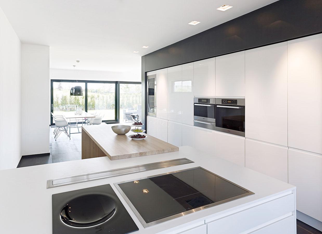 Jednoducho ačisto. Jednoznačné formy afarebnosť, typické pre exteriér domu, pokračujú aj vjeho interiéri. Mladá rodina sdvoma deťmi si vkuchyni zvolila elegantnú kombináciu praktického umelého kameňa, odolného bieleho laku apríjemného povrchu olejovaného dreva. Selegantným interiérom ladia aj sivé hliníkové rámy zasklení.