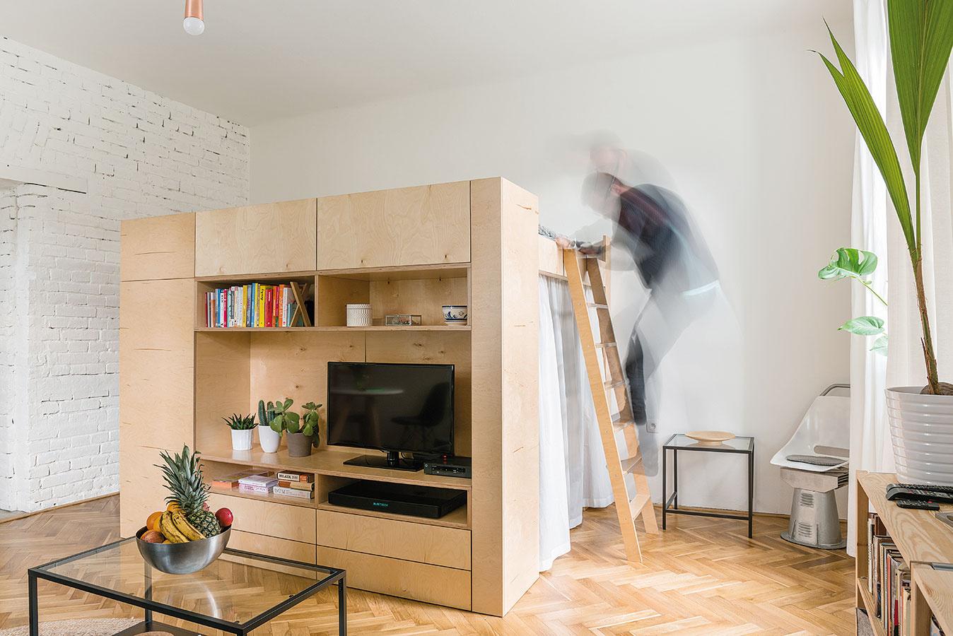 4 v1. Vstavaný kubus rozdelil veľkú miestnosť tak, že každá zo štyroch funkcií – šatník, obývačka, spálňa apracovňa – získala vlastný jasne definovaný priestor aj potrebné súkromie.