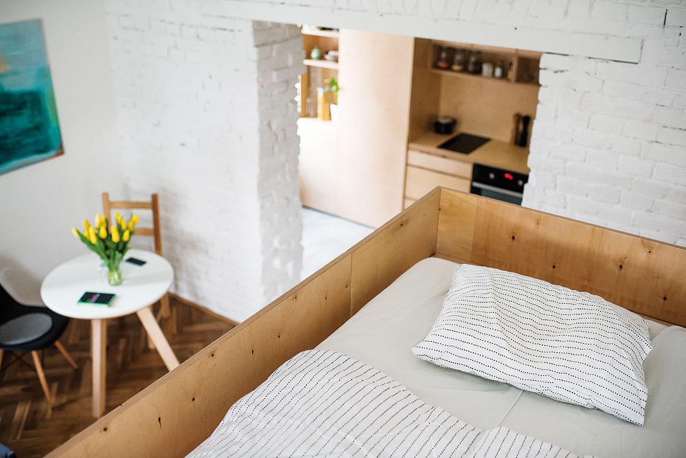 """Spanie """"na poschodí"""" je príjemne skryté pred zrakmi prichádzajúcich. Nápad so vstavanou vyvýšenou spálňou pritom architekti využili viacnásobne – na funkčné rozčlenenie miestnosti aj na vytvorenie odkladacích priestorov."""