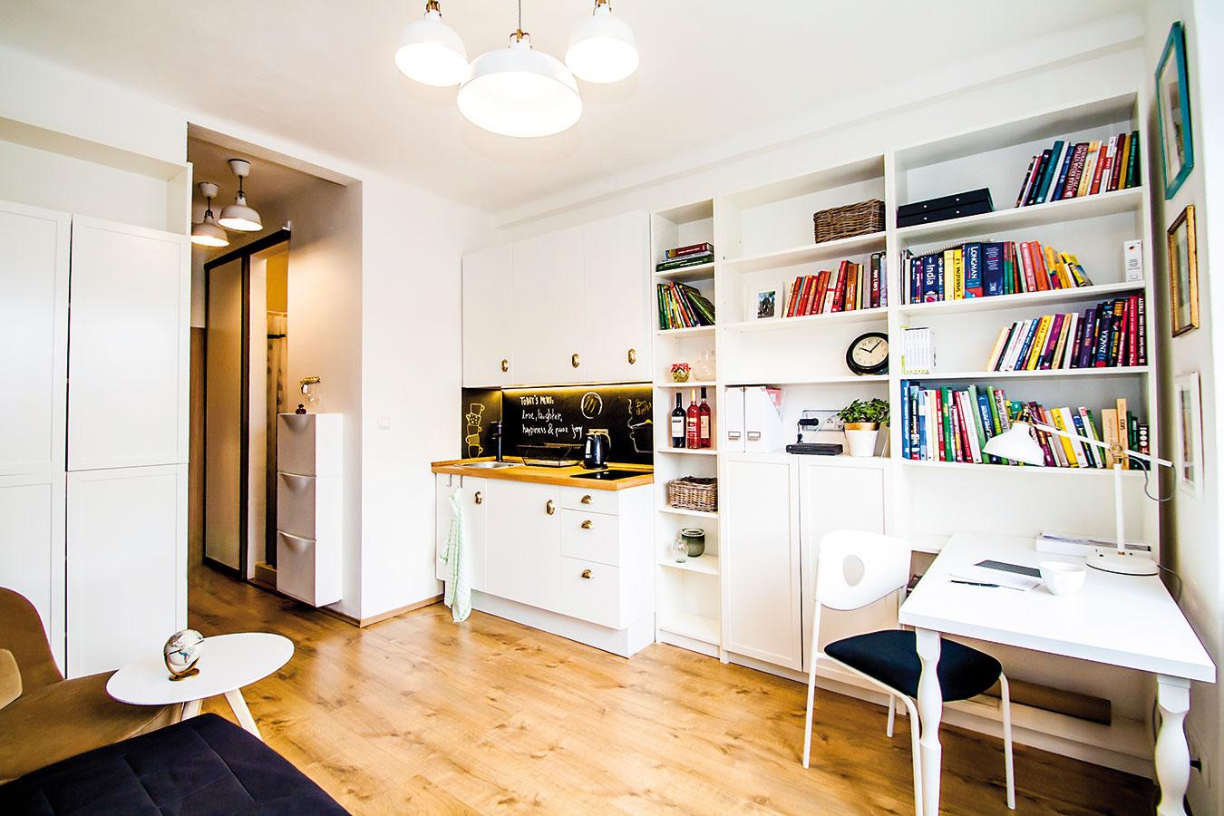 Nenápadná kuchyňa. Kuchynská linka dizajnovo dôsledne zakomponovaná do nábytkovej zostavy je vhodná, ak sa vpriestore varí povedzme len raz denne. Účel splní anezaberie vizuálne veľa miesta.