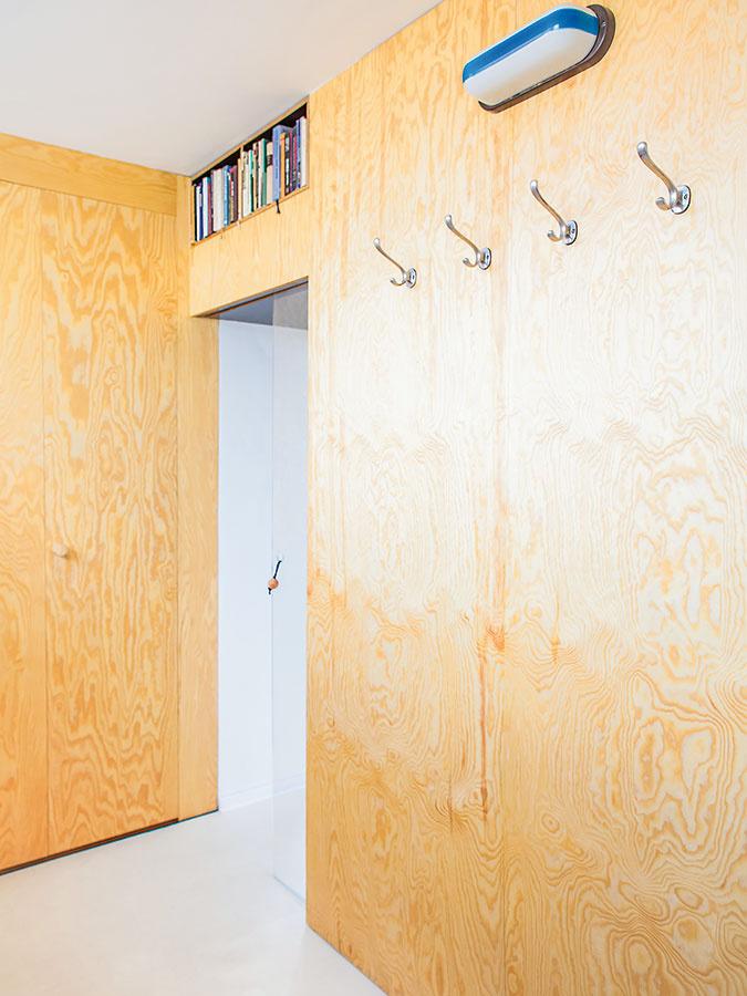 Zádverie bytu je obložené preglejkou, ktorá sta stala hlavným materiálom pri jeho zariaďovaní. Sympatickým prvkom je polica nad dverami vedúcimi do hlavnej obytnej časti aj zvolené svietidlo.