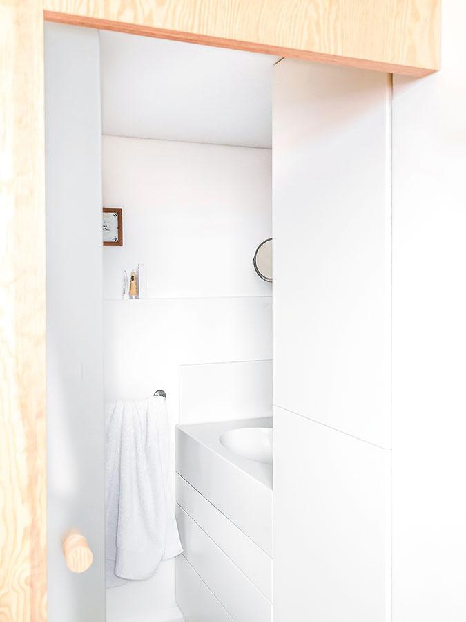 Kúpeľňa sa nesie vbielej farbe, čo ju opticky zväčšuje. Vaňu nahradil sprchovací kút, ktorý bol jednou zpožiadaviek investora. Asymetrické umývadlo vkúpeľni aj pracovná doska vkuchyni sú vyrobené zumelého kameňa Corianu.