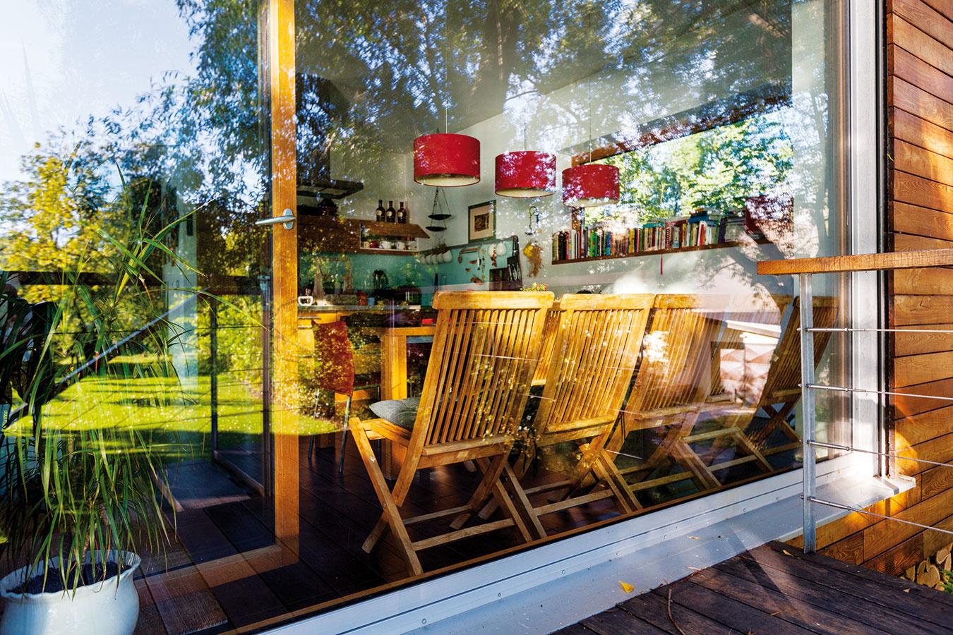 SKLENENÁ STENA opticky neruší: vonkajšie sedenie na celodrevenej terase sa takto prepojilo spriestorom obývačky, jedálne akuchyne.