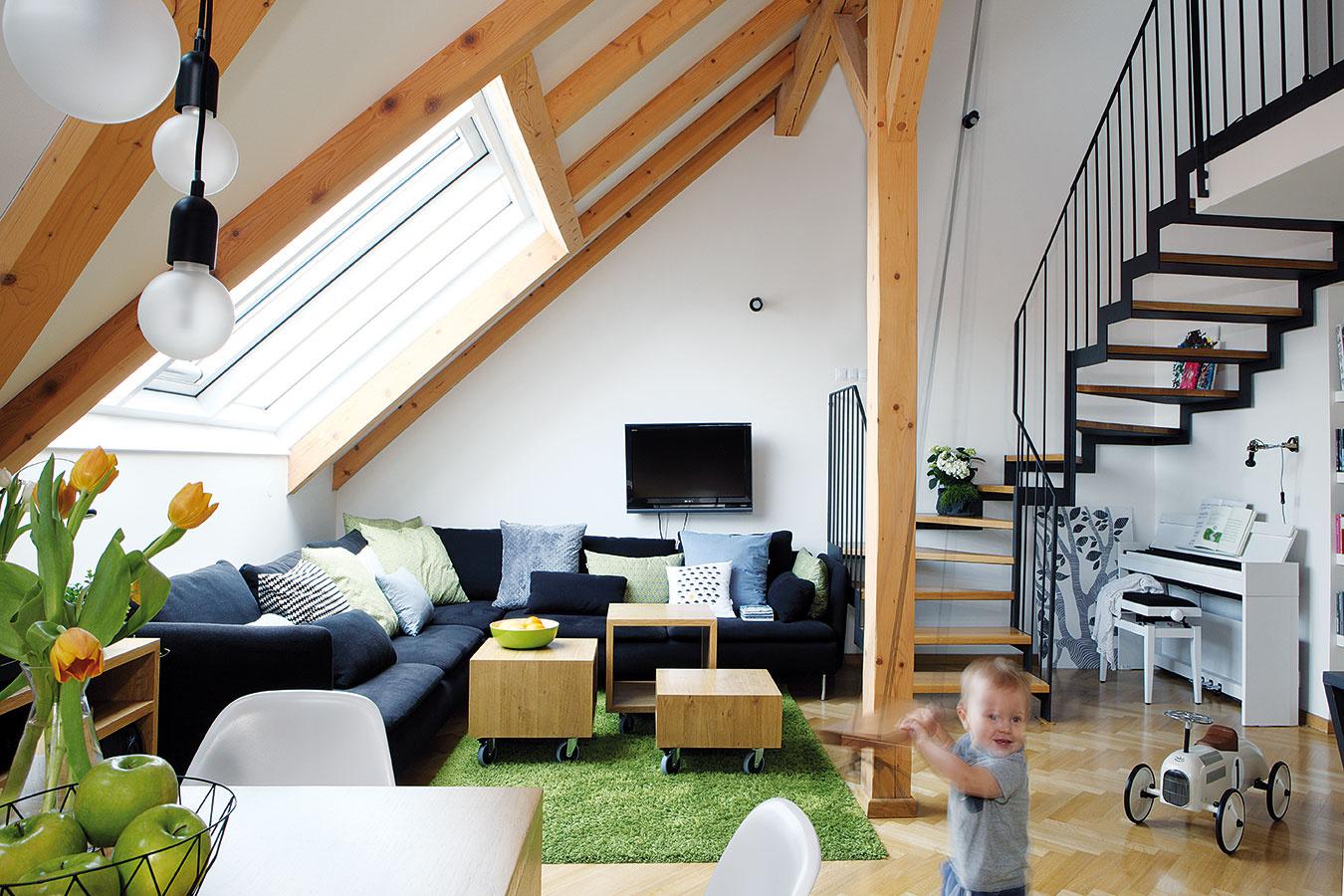 Pod strešnými oknami vdennej časti je umiestnená rohová sedacia súprava doplnená trojicou tvarovo jednoduchých stolíkov rôznej výšky na kolieskach. Doplnkovou farbou je svieža zelená, ktorá sa objavuje na vankúšoch aj na koberci svyšším vlasom.