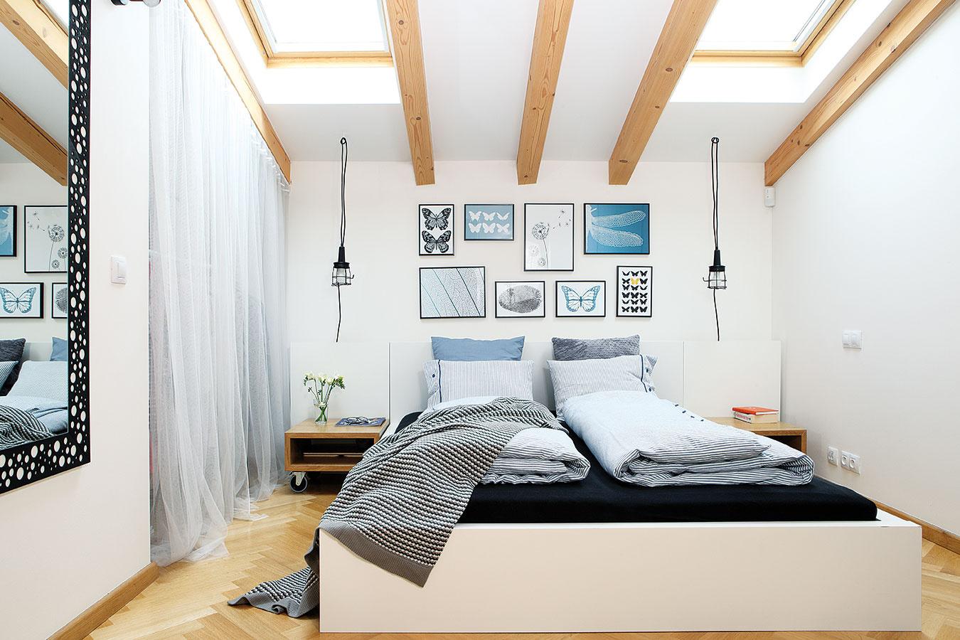 Vjemne pôsobiacej spálni dopĺňa základnú paletu bielej, čiernej aodtieňov dreva upokojujúca modrá. Príjemným akcentom sú zo šikminy visiace svietidlá nahrádzajúce štandardné stolové lampy.