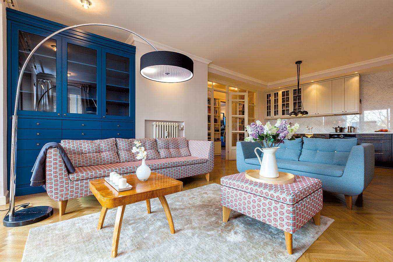 Kuchyňa ako pozadie obývacej izby pomocou dizajnu ladne zapadne do priestoru. Pomyselnú hranicu medzi týmito priestormi tvorí sedačka otočená chrbtom ku kuchyni.