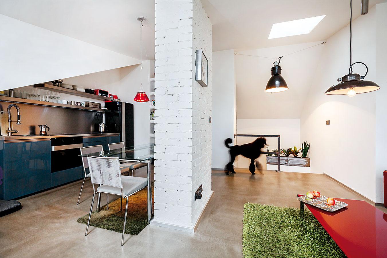 Náznak steny v strede dispozície má hneď niekoľko funkcií. Síce priestor na varenie oddelí, no neodseparuje, pomôže s umiestnením jedálenského stola, ako aj orientáciou sedačky, keďže takáto stienka je vhodná na zavesenie TV.