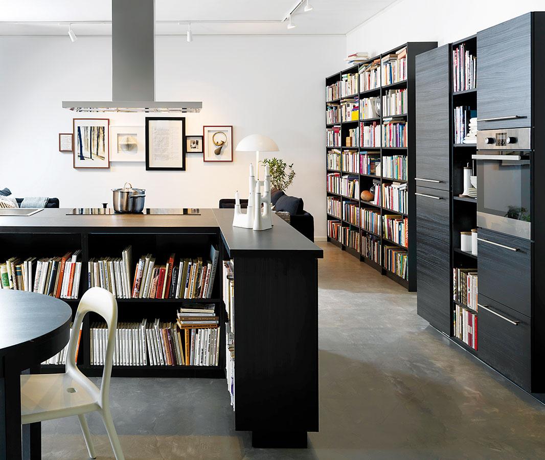 PRE KNIHOMOĽOV. Jedným zo spôsobov, ako urobiť z kuchyne obývaciu izbu, je využiť knihy. Všade. Tých zopár políc s dózami sa pri takom množstve literatúry celkom stratí. Dôležité je však mať prehľad.
