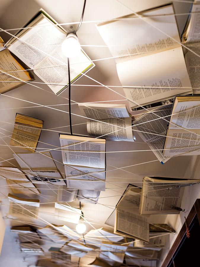 """Nápaditým oživením chodby prepájajúcej prvé dve miestnosti sú """"lietajúce"""" knihy na strope – do stien tesne pod stropom postačí ukotviť háky, obmotať okolo nich pevnejší motúz anaň potom naukladať otvorené knihy."""