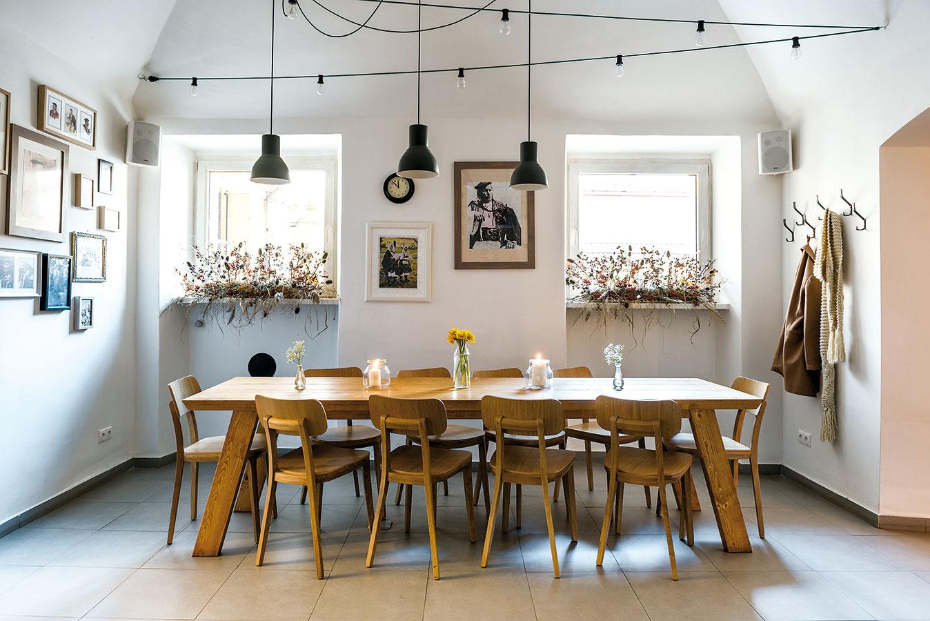 Rozľahlý stôl vstrednej miestnosti si majitelia nechali vyrobiť na mieru. Môžu ho využiť  jednotlivci pri práci avýborne poslúži aj pre väčšie partie ako co-workingový.
